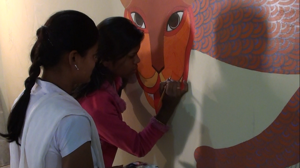 The girls get a chance to attempt painting the mural