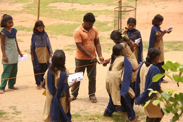 Our driver, Dinesh, too joins the team and helps students measure the Teak tree rope.