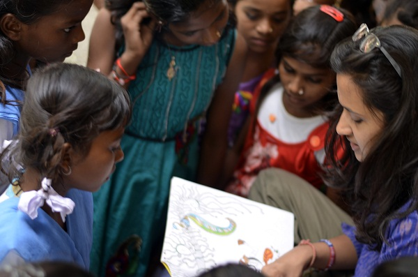The students in a small book reading with Pooja while they await their pick up.