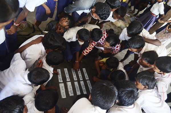 Our volunteer, Divya Nawale, with a group of students in the Water Footprint game. The students were meant to go on a trial, find their respective groups cards and match each item on the card to its water footprint. (Image: Monica Szczupider)